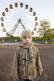 Little cute boy outside in park near carousel Royalty Free Stock Photography