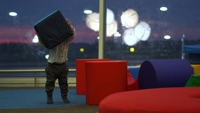 Little cute boy playing with big cubes in a children`s play area at the airport. Little cute boy playing with big cubes in a children`s play area among large stock video footage