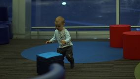 Boy playing with big cubes in a children`s play area at the airport, slow motion. Little cute boy playing with big cubes in a children`s play area among large stock video