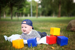 Little cute boy playing with blocks in summer park Royalty Free Stock Images