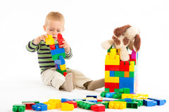 Little cute boy playing with building blocks. Isol. Little cute boy playing with plastic building blocks. Isolated on white Stock Images
