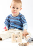 Little cute boy playing with building blocks. Isol. Little cute boy playing with wooden building blocks. Isolated on white Royalty Free Stock Photos