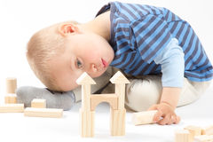 Little cute boy playing with building blocks. Isol. Little cute boy playing with wooden building blocks. Isolated on white Royalty Free Stock Images