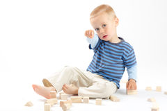 Little cute boy playing with building blocks. Isol. Little cute boy playing with wooden building blocks. Isolated on white Stock Image