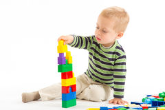 Little cute boy playing with building blocks. Isolated on white. Stock Image