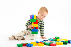Little cute boy playing with building blocks. Isolated on white. Little cute boy playing with plastic building blocks. Isolated on white stock photography