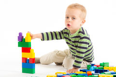 Little cute boy playing with building blocks. Isolated on white. Little cute boy playing with plastic building blocks. Isolated on white Stock Images