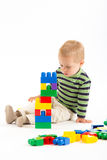 Little cute boy playing with building blocks. Isolated on white. Little cute boy playing with plastic building blocks. Isolated on white royalty free stock photos
