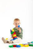 Little cute boy playing with building blocks. Isolated on white. Royalty Free Stock Image
