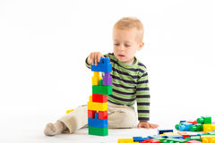 Little cute boy playing with building blocks. Isolated on white. Little cute boy playing with plastic building blocks. Isolated on white Royalty Free Stock Image