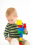 Little cute boy playing with building blocks. Isolated on white. Little cute boy playing with plastic building blocks. Isolated on white Stock Image