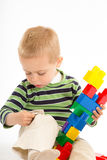 Little cute boy playing with building blocks. Isolated on white. Stock Images