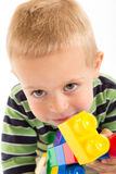 Little cute boy playing with building blocks. Isolated on white. Little cute boy playing with plastic building blocks. Isolated on white stock photo