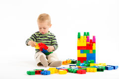 Little cute boy playing with building blocks. Isolated on white. Little cute boy playing with plastic building blocks. Isolated on white stock photos