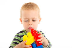 Little cute boy playing with building blocks. Isolated on white. Royalty Free Stock Photo