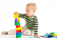 Little cute boy playing with building blocks. Isolated on white. Little cute boy playing with plastic building blocks. Isolated on white royalty free stock photography