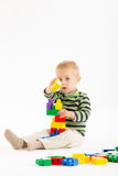 Little cute boy playing with building blocks. Isolated on white. Little cute boy playing with plastic building blocks. Isolated on white Royalty Free Stock Images