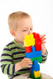 Little cute boy playing with building blocks. Isolated on white. Stock Photo