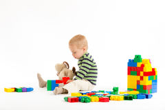 Little cute boy playing with building blocks. Isolated on white. Little cute boy playing with plastic building blocks and plush puppy. Isolated on white royalty free stock photography