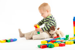 Little cute boy playing with building blocks. Isolated on white. Little cute boy playing with plastic building blocks and plush puppy. Isolated on white Royalty Free Stock Images