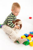 Little cute boy playing with building blocks. Isolated on white. Little cute boy playing with plastic building blocks and plush puppy. Isolated on white stock image
