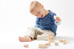 Little cute boy playing with building blocks. Isolated on white. Little cute boy playing with wooden building blocks. Isolated on white Royalty Free Stock Photos