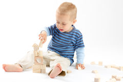 Little cute boy playing with building blocks. Isolated on white. Little cute boy playing with wooden building blocks. Isolated on white Stock Photo