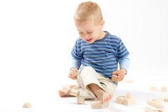 Little cute boy playing with building blocks. Isolated on white. Royalty Free Stock Photography