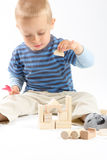 Little cute boy playing with building blocks. Isolated on white. Little cute boy playing with wooden building blocks. Isolated on white Royalty Free Stock Images
