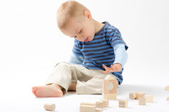 Little cute boy playing with building blocks. Isolated on white. Little cute boy playing with wooden building blocks. Isolated on white stock image