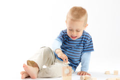 Little cute boy playing with building blocks. Isolated on white. Little cute boy playing with wooden building blocks. Isolated on white Stock Photography