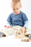 Little cute boy playing with building blocks. Isolated on white. Little cute boy playing with wooden building blocks. Isolated on white Royalty Free Stock Photo