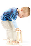 Little cute boy playing with building blocks. Isolated on white. Little cute boy playing with wooden building blocks. Isolated on white Royalty Free Stock Photography