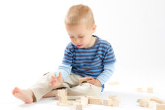 Little cute boy playing with building blocks. Isolated on white. Little cute boy playing with wooden building blocks. Isolated on white Stock Images