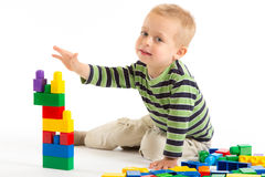 Little cute boy playing with building blocks.  on white. Little cute boy playing with plastic building blocks.  on white Stock Photography