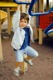 Little cute boy playing on playground, hanging on gymnastic ring Stock Images
