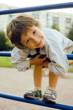 Little cute boy playing on playground, hanging on gymnastic ring Stock Image