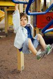 Little cute boy playing on playground, hanging on gymnastic ring Stock Photography