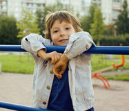 Little cute boy playing on playground, hanging on gymnastic ring Royalty Free Stock Photos