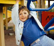 Little cute boy playing on playground, hanging on gymnastic ring Royalty Free Stock Photo