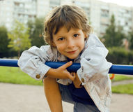 Little cute boy playing on playground, hanging on gymnastic ring Stock Photos