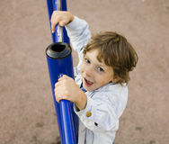 Little cute boy playing on playground, hanging on gymnastic ring Royalty Free Stock Photography
