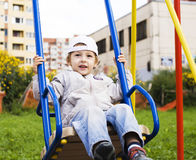 Little cute boy playing on playground, hanging on gymnastic ring Royalty Free Stock Image