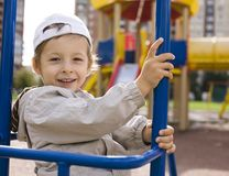 Little cute boy playing on playground, hanging on Royalty Free Stock Images