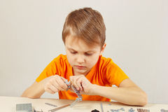 Little cute boy plays with mechanical kit at table Stock Image
