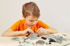 Little cute boy plays with mechanical starter kit at table Stock Images