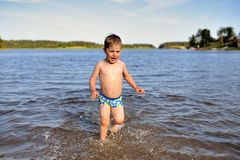 Little cute boy plays in water sunny day in lake Stock Images