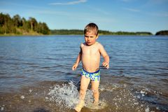 Little cute boy plays in water sunny day in lake Royalty Free Stock Photo