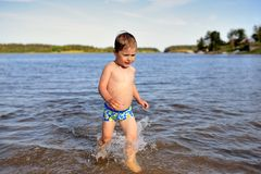 Little cute boy plays in water sunny day in lake Royalty Free Stock Image