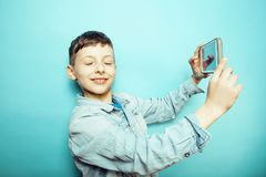 Little cute boy posing emotional on blue background with smartph. One, lifestyle people concept close up Royalty Free Stock Photos